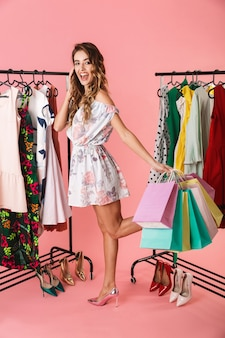 Adorable niña de pie en la tienda cerca del perchero y sosteniendo coloridas bolsas de compras aisladas en rosa