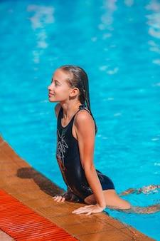Adorable niña en la piscina al aire libre