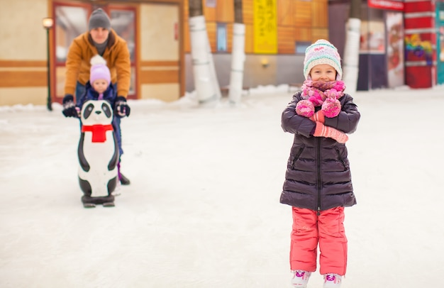 Adorable niña en la pista de patinaje con padre y hermana linda