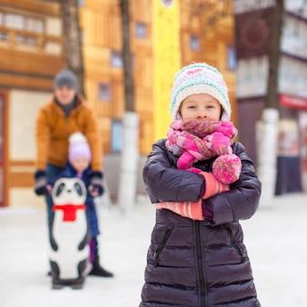 Adorable niña en la pista de patinaje, papá con hermana pequeña