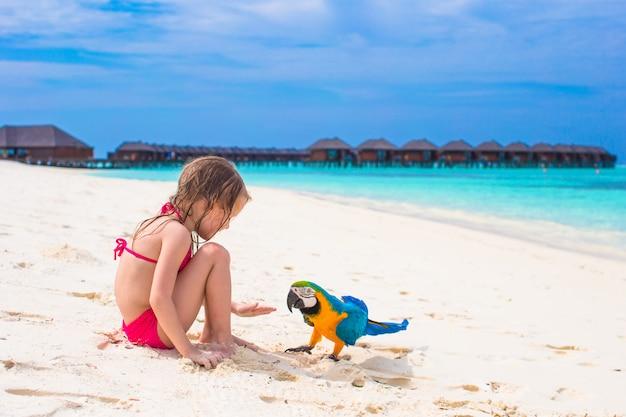 Adorable niña en la playa con gran colorido loro