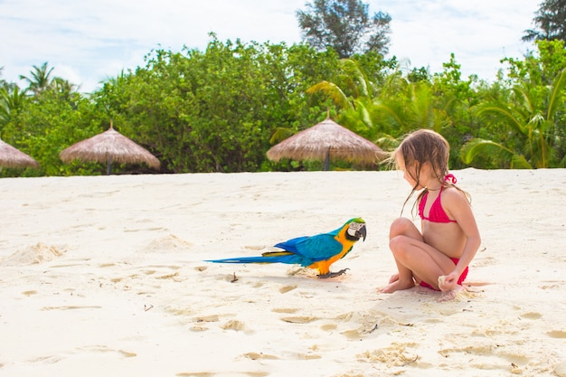 Adorable niña en la playa con loro colorido