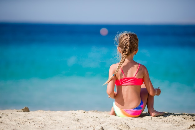 Adorable niña en la playa tropical durante las vacaciones