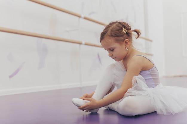 Adorable niña poniéndose los zapatos de baile de ballet, sentada en el suelo en el estudio de baile