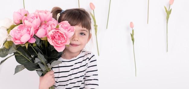 Adorable niña posando con rosas