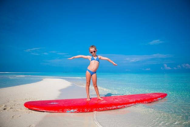 Adorable niña practica posición de surf en la playa