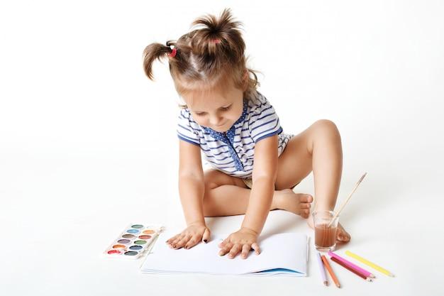 Adorable niña de preescolar con manos pintadas, hace huellas digitales en la página en blanco del álbum, usa acuarela para hacer fotos, es muy creativa, está aislada sobre la pared blanca del estudio