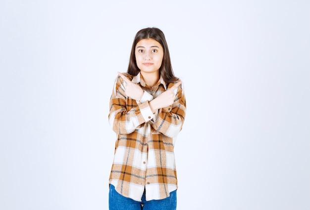Adorable niña en ropa casual posando sobre pared blanca.