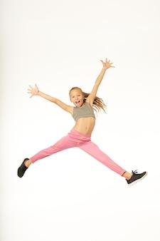 Adorable niña en ropa deportiva saltando en el aire y levantando los brazos. aislado sobre fondo blanco