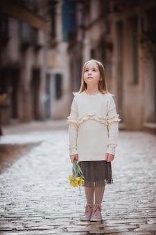 Adorable niña en ropa de tendencia de pie en el casco antiguo en un soleado día de primavera con flores amarillas