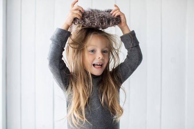 Adorable niña rubia jugando con sombrero de invierno