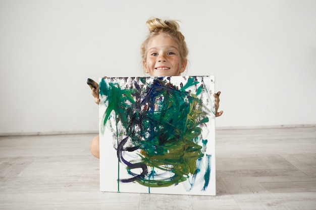 Adorable niña rubia sonriente hading por la imagen. linda niña con moño y pecas posando contra la pared blanca. la sonrisa infantil es una fuente de emociones positivas.