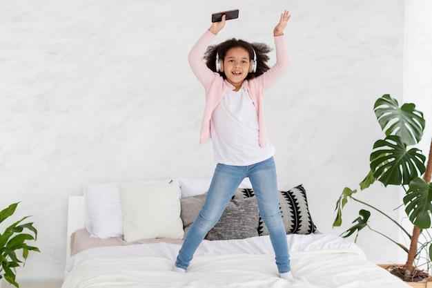 Adorable niña saltando en la cama en su casa