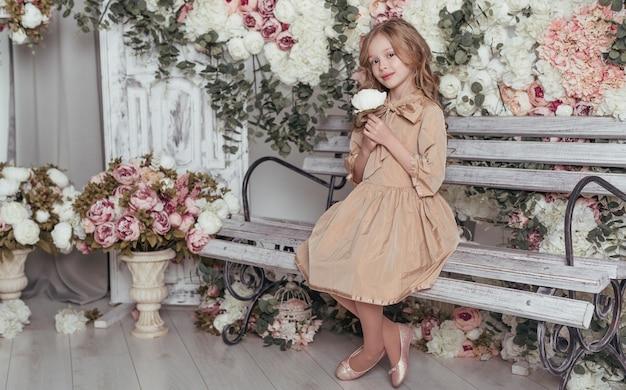 Adorable niña sentada en un banco