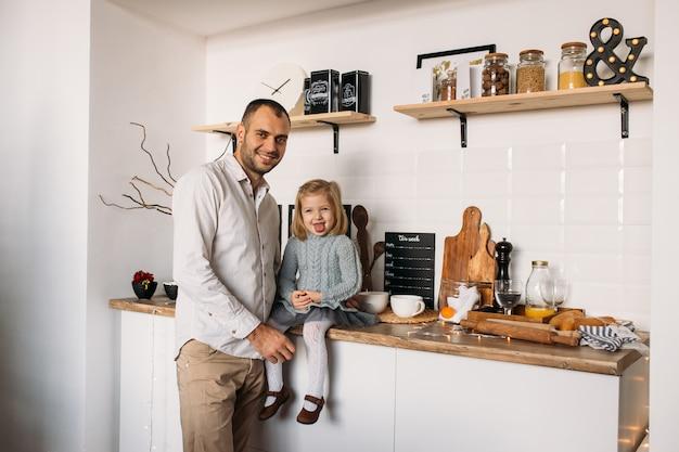 Adorable niña está sentada en la mesa de la cocina con el padre.