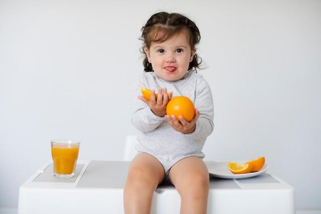 Adorable niña sentada y mostrando sus naranjas