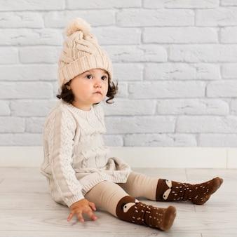 Adorable niña sentada en el piso