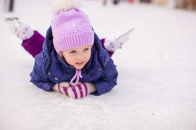 Adorable niña sentada sobre hielo con patines después de la caída