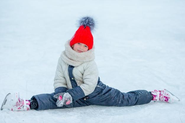 Adorable niña sentada sobre hielo con patines después del otoño