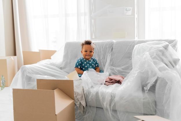 Adorable niña sentada en su antigua casa antes de mudarse
