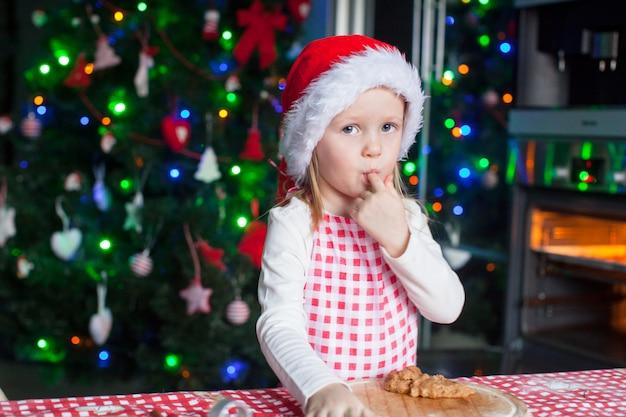 Adorable niña con sombrero de santa comiendo la masa para galletas de jengibre