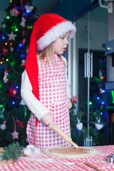 Adorable niña con sombrero de santa hornear galletas de navidad de pan de jengibre en casa