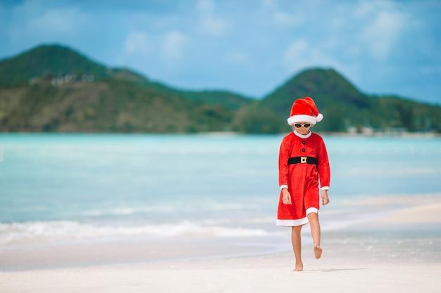 Adorable niña con sombrero de santa en playa tropical