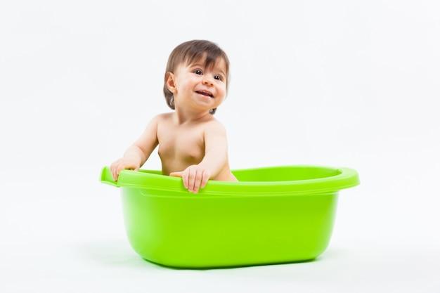 Adorable niña sonriente caucásica tomando baño en tina verde sobre blanco