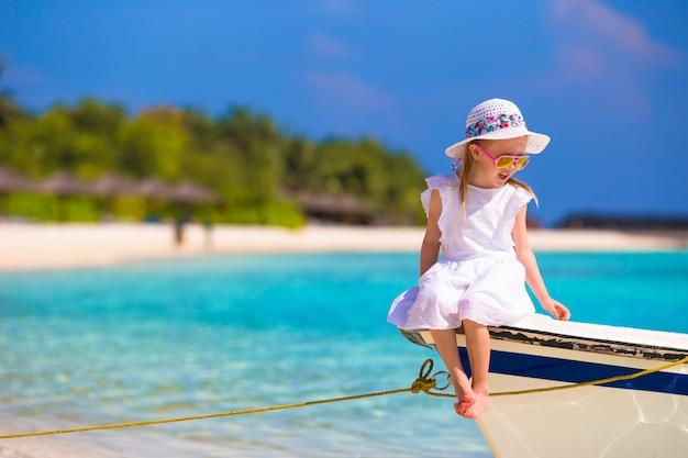 Adorable niña sonriente feliz en barco en el mar