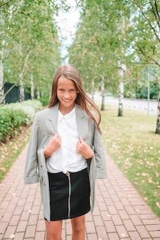 Adorable niña sonriente posando delante de su escuela. adorable niña que se siente muy emocionada por volver a la escuela