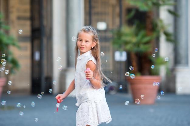 Adorable niña soplando pompas de jabón en trastevere en roma, italia