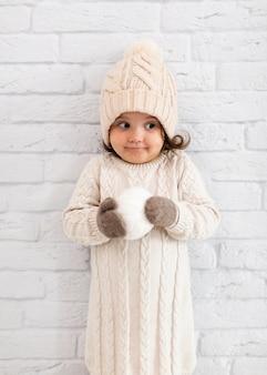 Adorable niña sosteniendo una bola de nieve