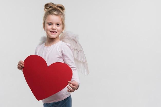 Adorable niña sosteniendo un corazón