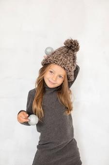 Adorable niña sosteniendo globos de navidad