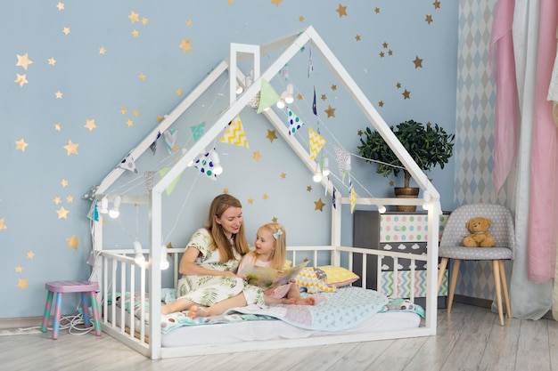 Adorable niña y su joven madre están leyendo un libro y sonriendo mientras están sentados en la cama de la casa decorada en el dormitorio