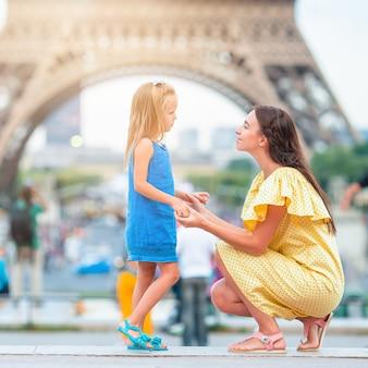 Adorable niña y su joven madre en parís cerca de la torre eiffel durante las vacaciones de verano