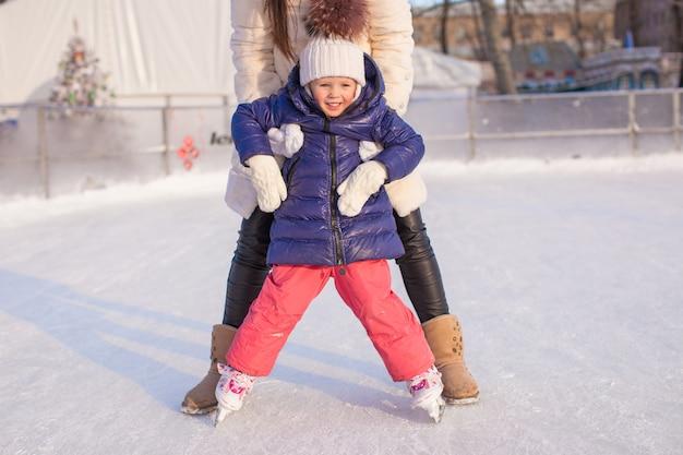 Adorable niña con su madre aprendiendo a patinar