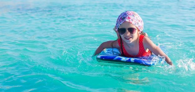 Adorable niña en una tabla de surf en el mar turquesa