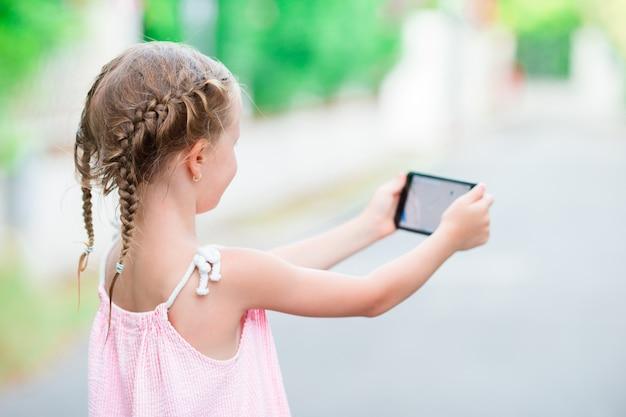 Adorable niña con teléfono durante las vacaciones de verano al aire libre