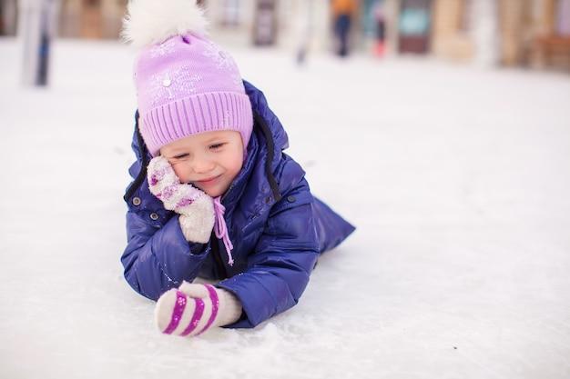 Adorable niña tendida en la pista de patinaje después de la caída