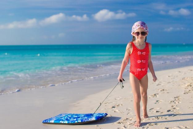 Adorable niña tira una tabla de surf en la costa blanca