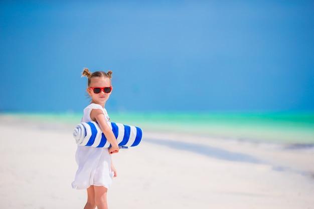 Adorable niña con toallas en vacaciones tropicales