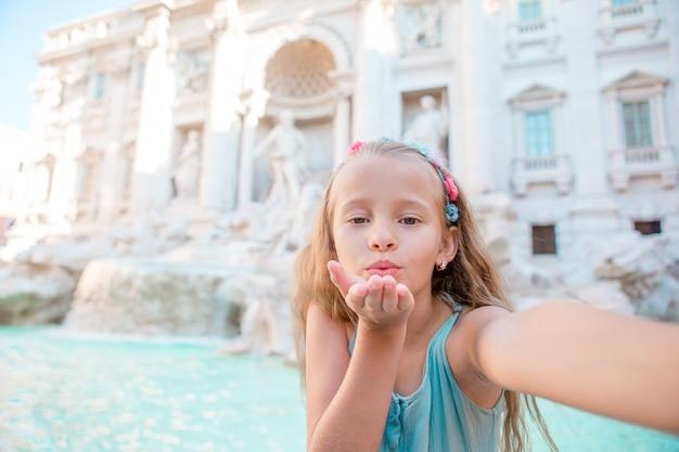 Adorable niña tomando selfie junto a la fuente de trevi en roma.