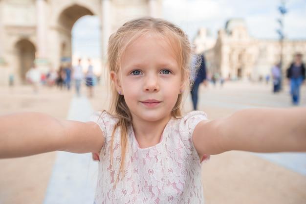 Adorable niña tomando selfie con teléfono móvil al aire libre en parís