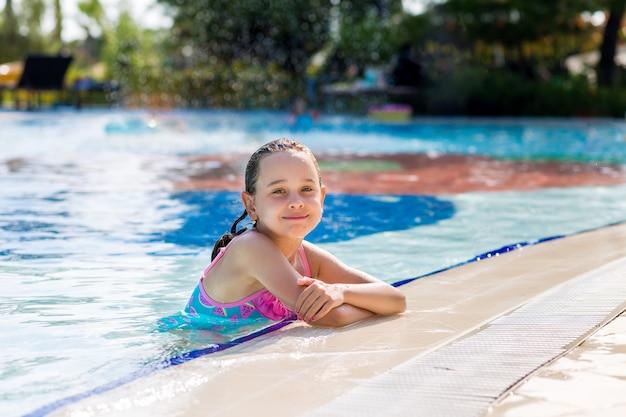 Adorable niña en traje de baño brillante en la piscina de vacaciones en un día soleado de verano. concepto de vacaciones familiares