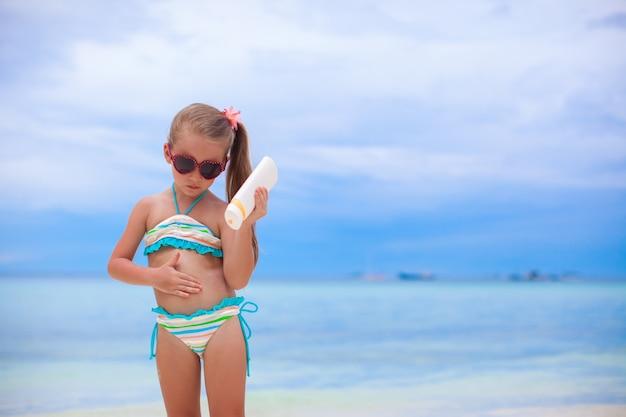 Adorable niña en traje de baño tiene botella de loción bronceadora