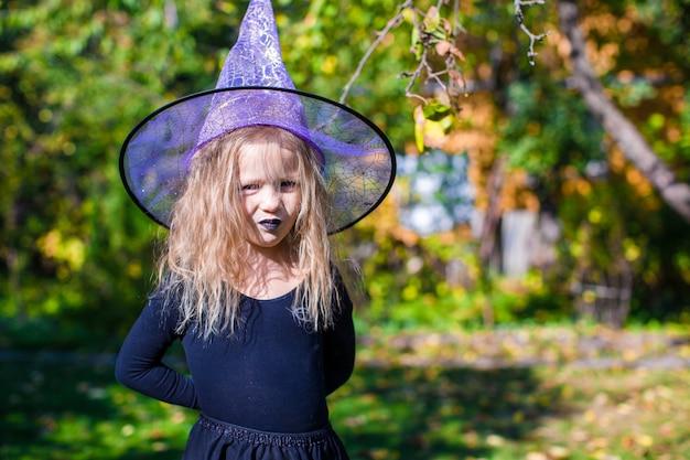 Adorable niña en traje de bruja lanza un hechizo en halloween
