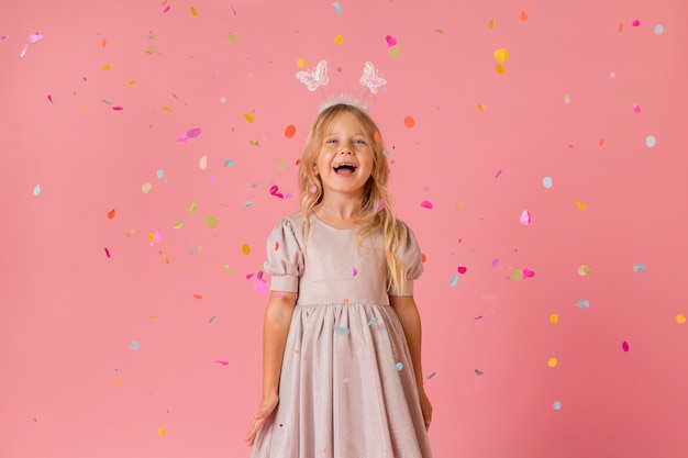 Adorable niña en traje con confeti