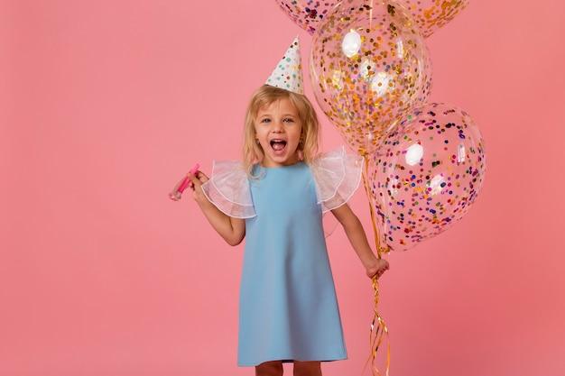 Adorable niña en traje con globos