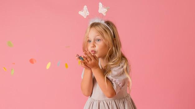 Adorable niña en traje soplando confeti